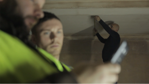 electrician film, three men on site. one is working the other two are looking at a mobile phone
