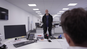 electrician film, two men. one sat behind an office desk the other stood up in front of him