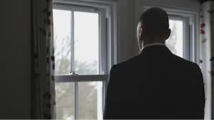 electrician film, man stood in living room staring out of window with his back to us