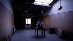 artificial dreams, man sat on desk holding a book of photos
