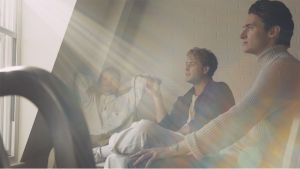 three Male band members sat together in front of window