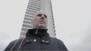 electrician film, man walking across an estate with block of flats behind him