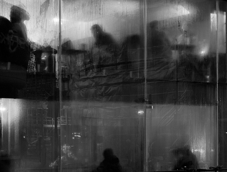 black and white reflective shot from street looking inside of steamy windows of people sat at tables working