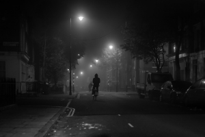 hooded person riding a bike in london at night