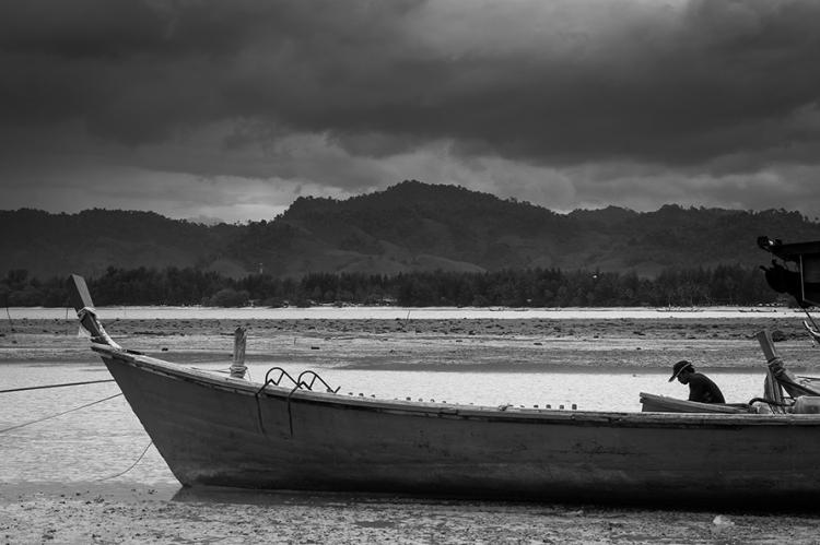 Man sat in Boat on beach