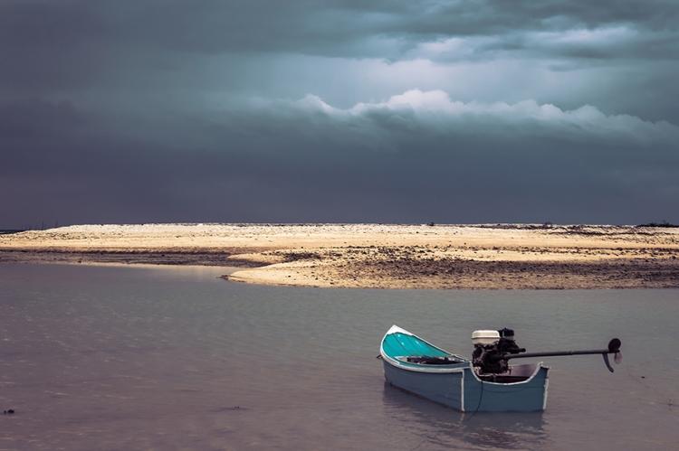 Empty small speedboat drifting on ocean water by beach