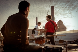 3 male members of a music band on a roof with instruments